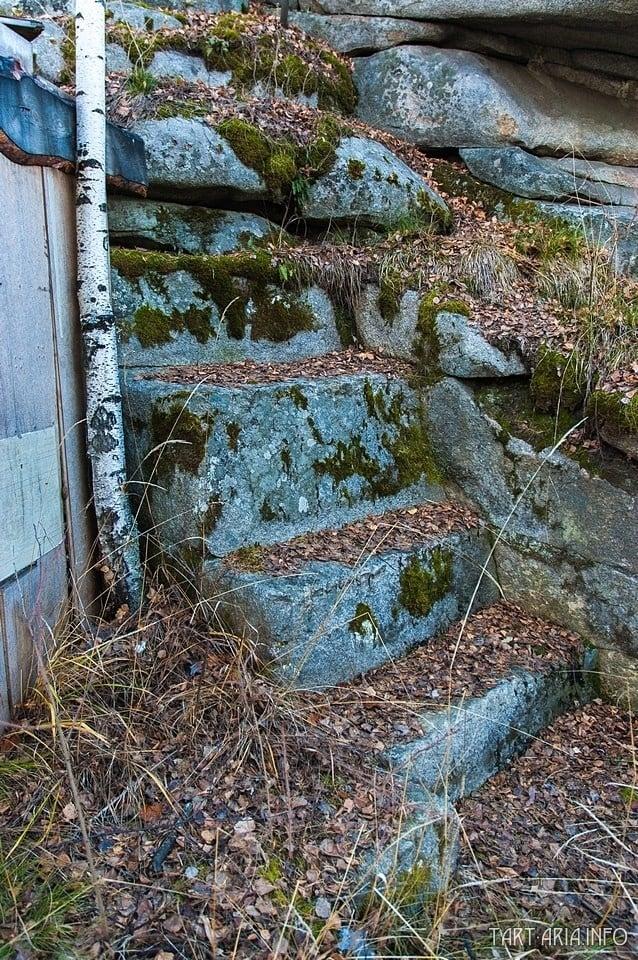 Detail schodiště vyčnívající pod skalním útvarem