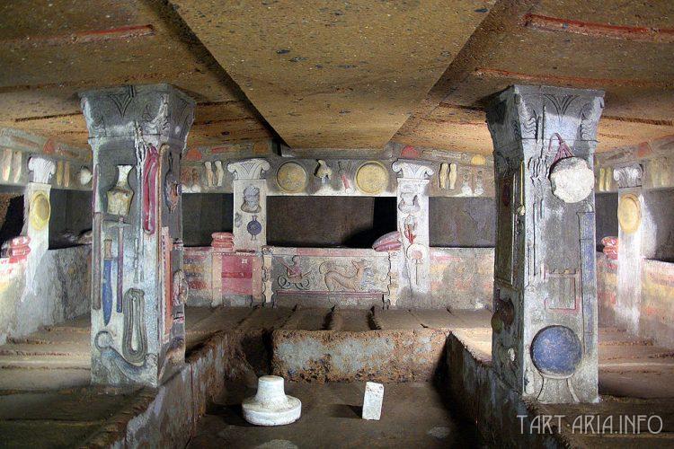 Интерьер гробницы, содержащей этрусские предметы, вырезанные в вулканической туфовой скале, а также отдельные погребальные камеры с каменными подушками, IV век до н.э., Некрополи делла Бандитачча, Черветери, Италия. Источник